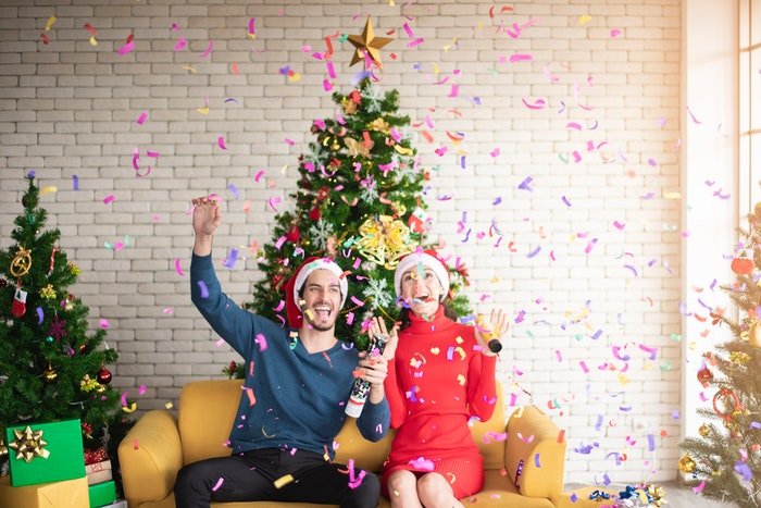 man and woman celebrating Christmas with a bottle